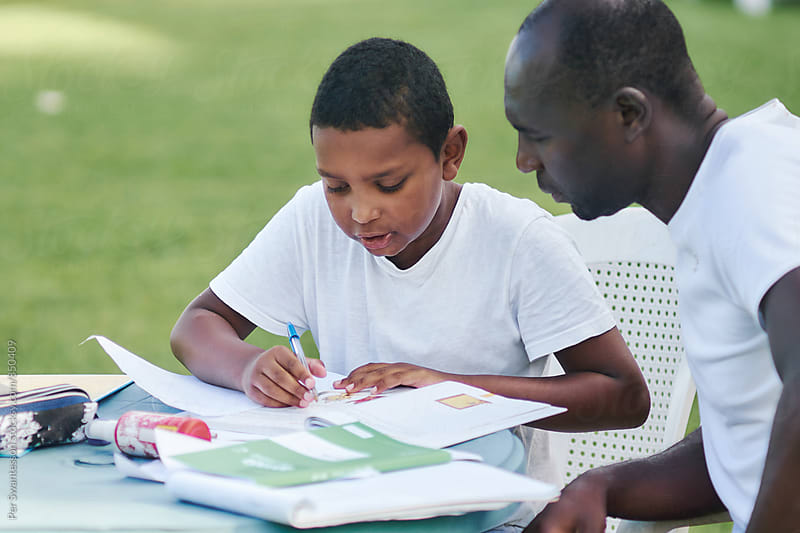 Father and son doing schoolwork together outdoors by Per Swantesson for Stocksy United