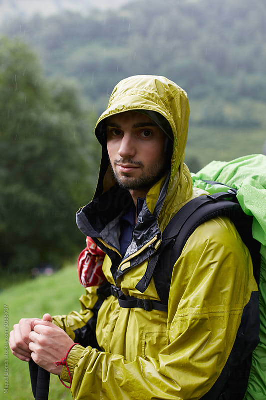 Portrait of a young man backpacker with rain clothing  by Miquel Llonch for Stocksy United