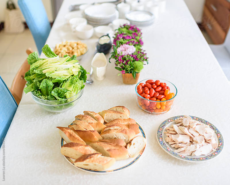 Breakfast buffet of bread, chicken, green salad, tomato and tableware by Lawren Lu for Stocksy United
