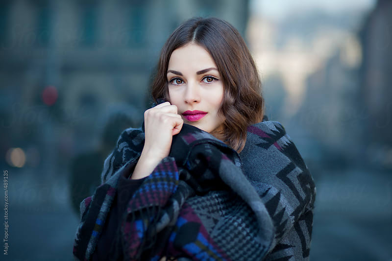 Young beautiful woman with black hair, scarf and red lipstick by Maja Topcagic for Stocksy United