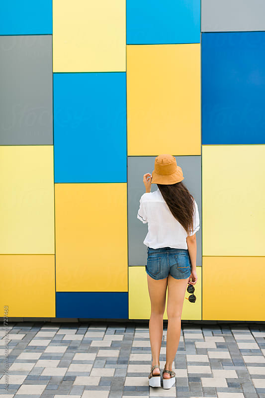 young woman with hat on the colorful background  by Alexey Kuzma for Stocksy United