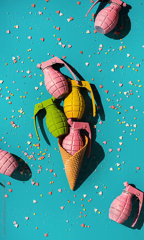 Ice cream made of colorful grenades with sprinkles in many colors on blue balckground by Marko Milanovic for Stocksy United