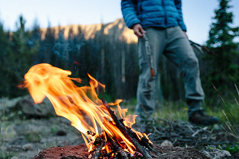 Man creating low impact fire outdoors by Matthew Spaulding for Stocksy United