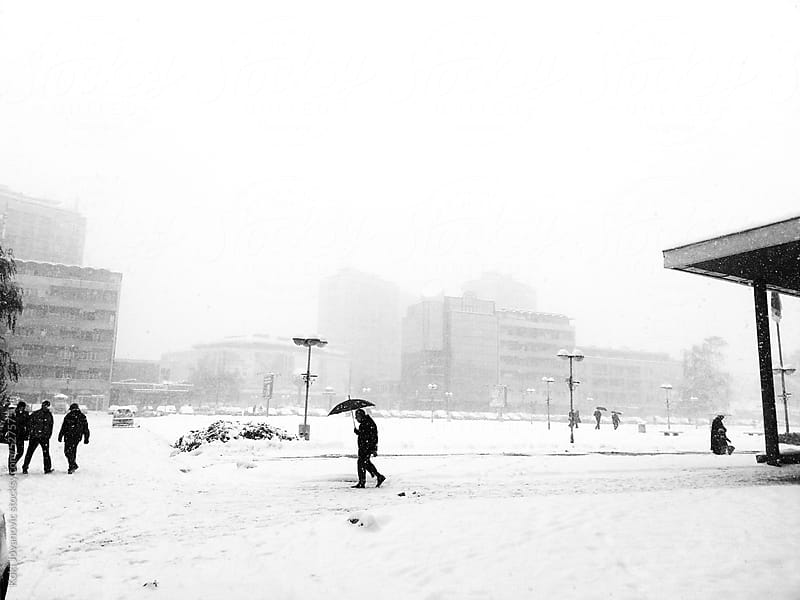 old man with umbrella outdoors In snowfall by Koki Jovanovic for Stocksy United