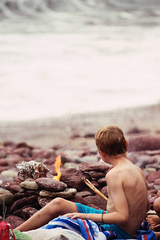 A boy sitting by a fire on a beach. by Helen Rushbrook for Stocksy United