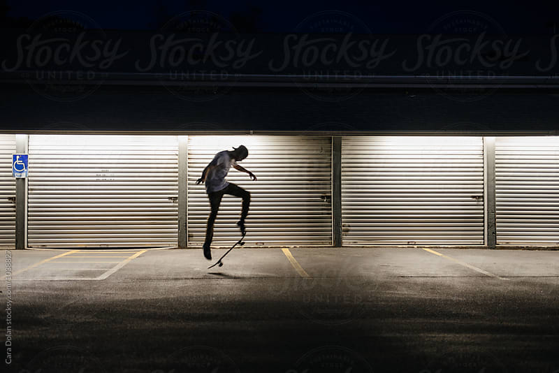 Skateboarder in a parking lot at night by Cara Slifka for Stocksy United