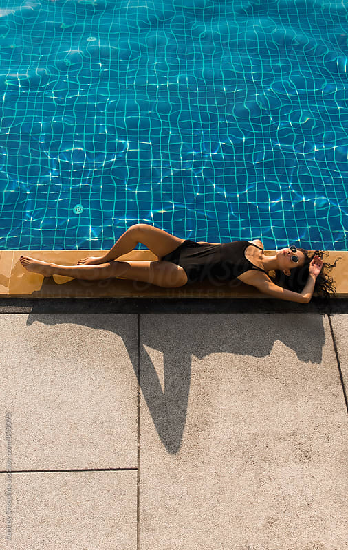 Beautiful young woman in black tricot sunbathing by the pool on hot summer day. by Marko Milanovic for Stocksy United