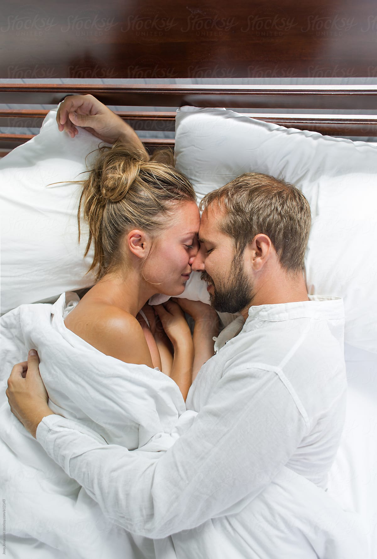 Couple sharing romantic moment in bed together by jovo jovanovic for stocksy united