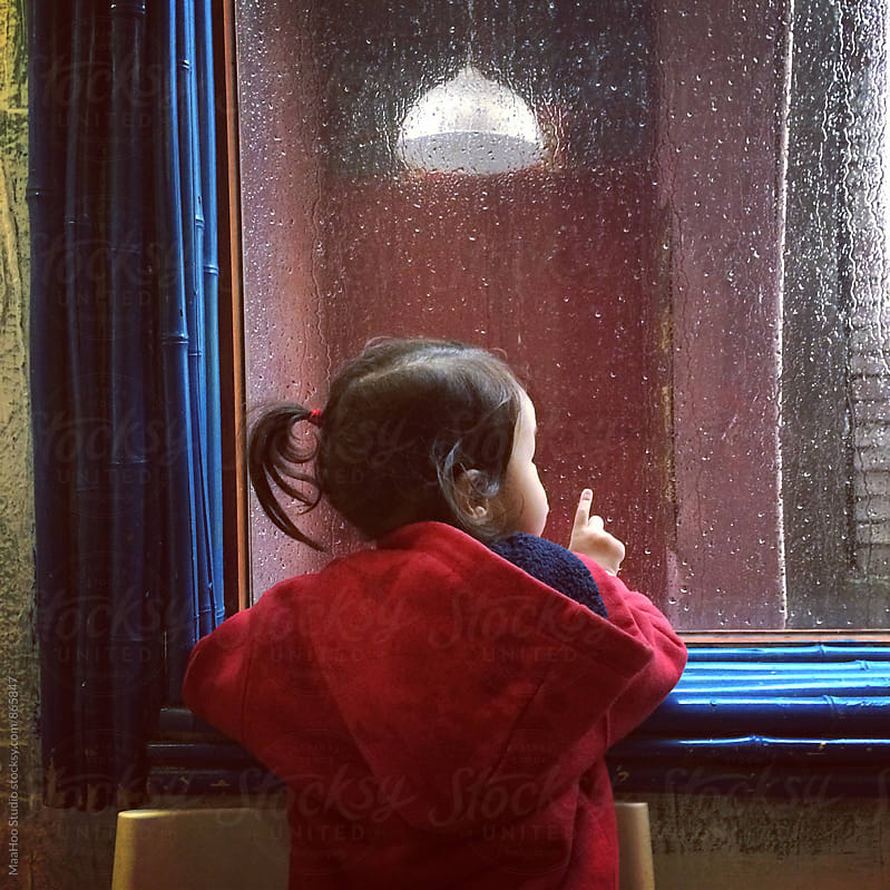 Young girl looking outside window in raining day by MaaHoo Studio for Stocksy United