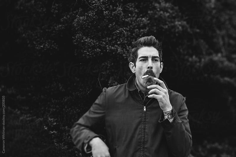 Man smoking a cigarette outdoors in black and white by Cameron Whitman for Stocksy United