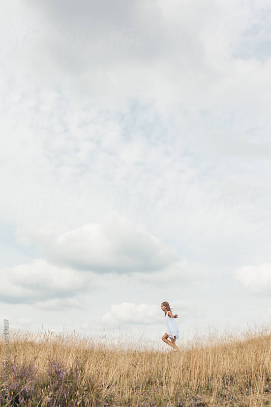 Little girl in a white dress running in a golden field against a big sky by Cindy Prins for Stocksy United