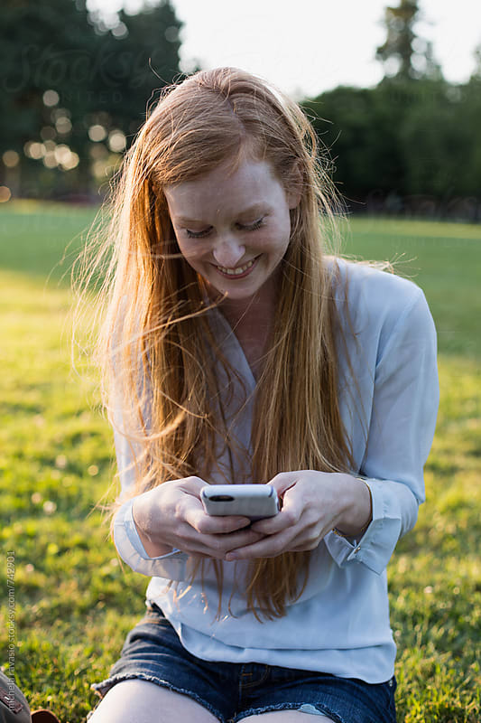 Beautiful girl using a smartphone outdoors by michela ravasio for Stocksy United