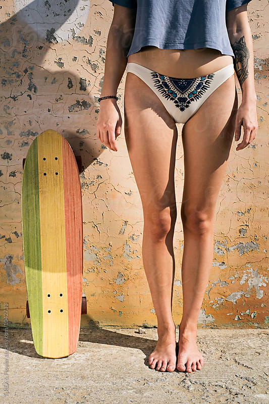 Barefoot girl in bikini pants near longboard by T-REX & Flower for Stocksy United