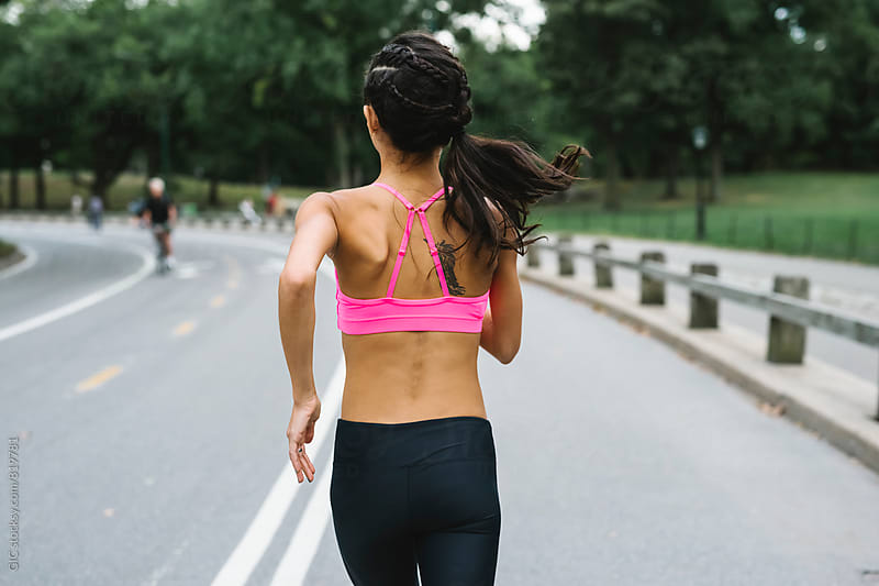 Young woman during jogging in Central Park, NY by Simone Becchetti for Stocksy United