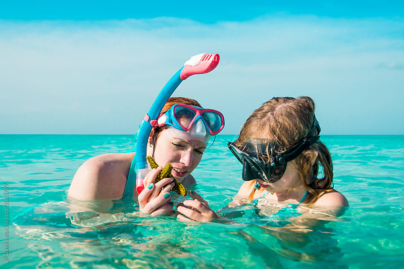 Mother and Daughter Looking at Starfish While Snorkeling on Tropical Beach at Resort by JP Danko for Stocksy United