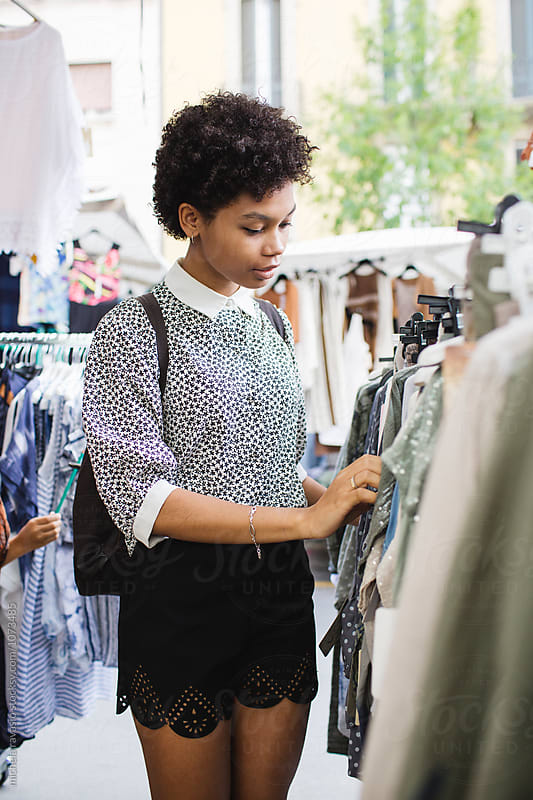 Afro woman shopping outdoors by michela ravasio for Stocksy United