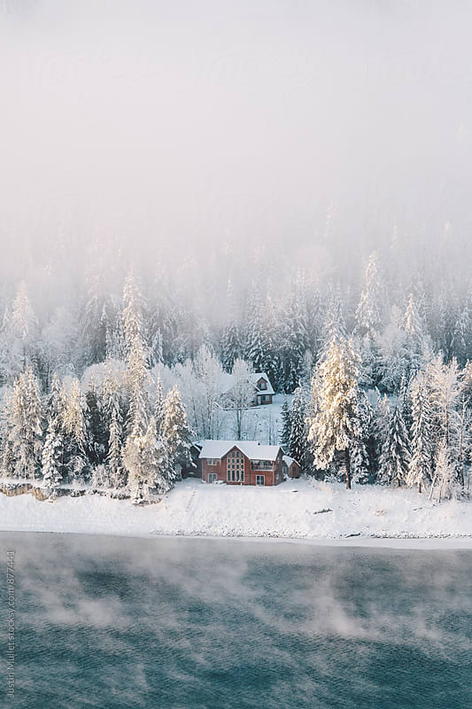 A foggy river landscape with a house nestled in the pine trees by Justin Mullet for Stocksy United
