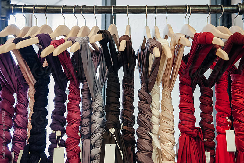 Rack of jersey cotton dresses on hangers tied up in braids by Cara Dolan for Stocksy United