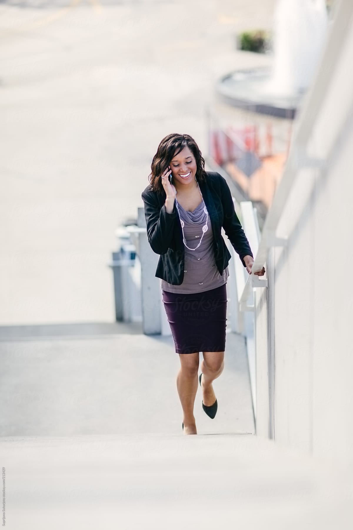 Stock Photo Happy African American Businesswoman Talking On The Phone Walking Up The Stairs
