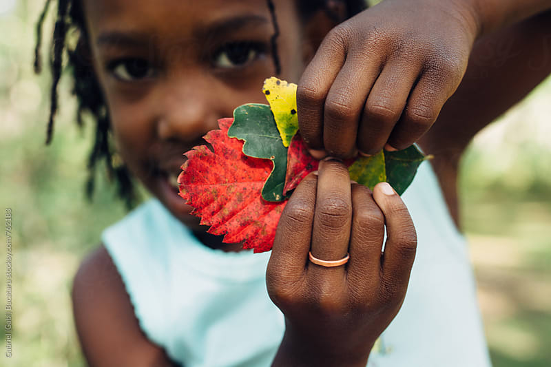 Cute black girl holding colorful fall leaves in her hands by Gabriel (Gabi) Bucataru for Stocksy United