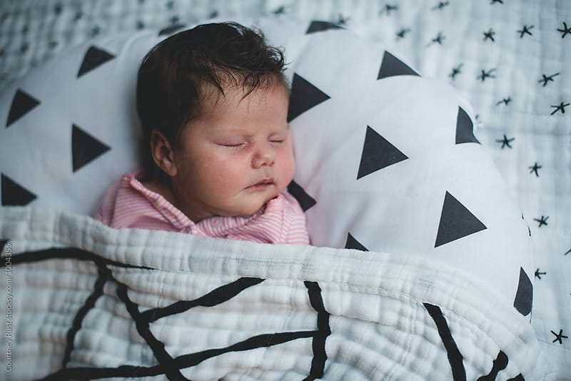Close up of baby sleeping on black and white fabric  by Courtney Rust for Stocksy United