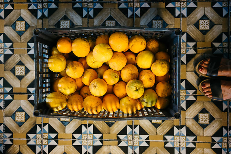Crate of oranges on floor, Greece by Kirstin Mckee for Stocksy United