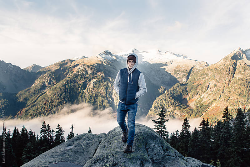 Young Man Wearing Beanie Walking Down From Rock Ledge In Mountains by Luke Mattson for Stocksy United