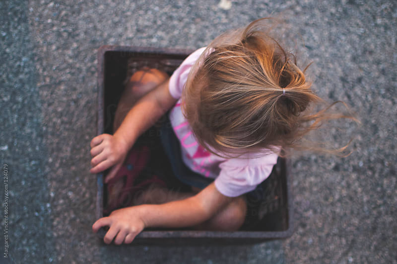 looking down on a little girl sitting in a milk crate by Margaret Vincent for Stocksy United