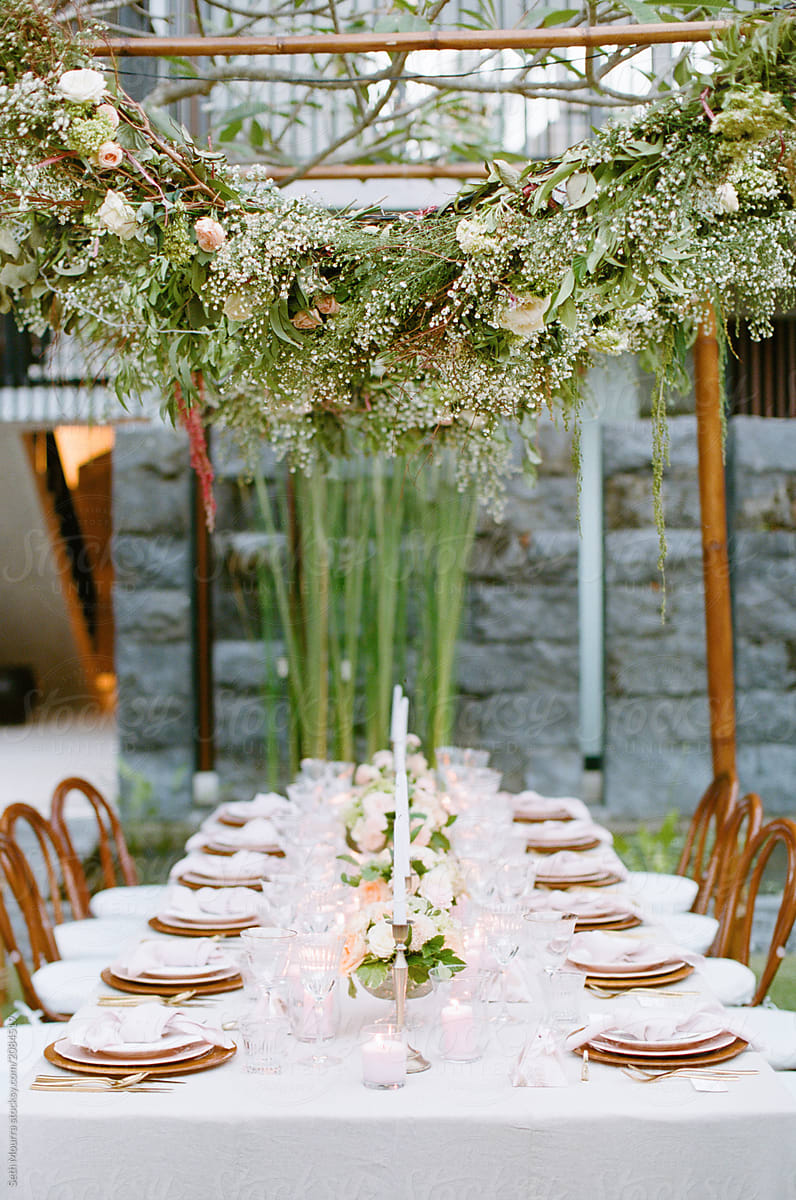 Outdoor, tropical wedding reception table with hanging greenery garlands by  Seth Mourra - Outdoors, Wedding reception - Stocksy United
