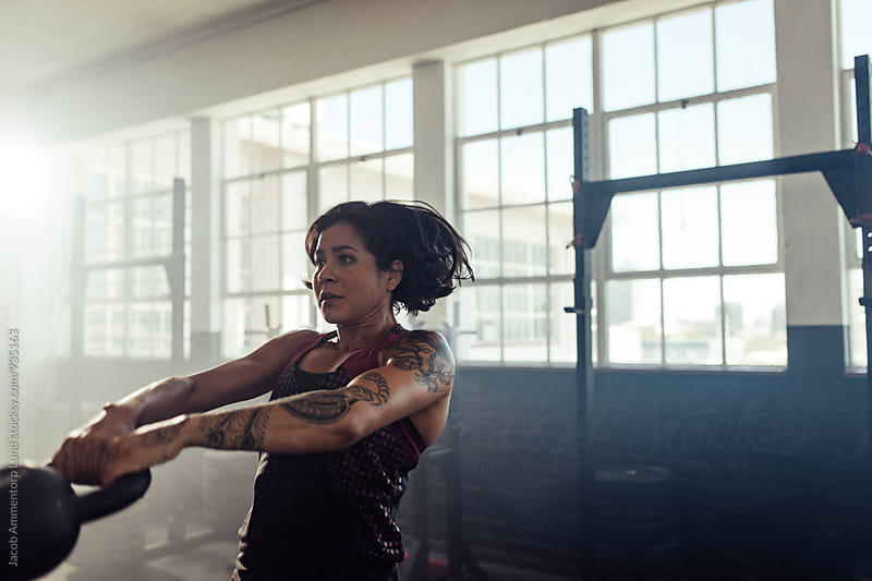 Fitness woman swinging a kettlebell at gym  by Jacob Ammentorp Lund for Stocksy United