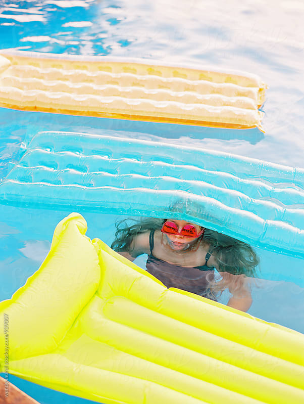colorful pool fun wtih girl under 3 rafts with sunglasses by wendy laurel for Stocksy United