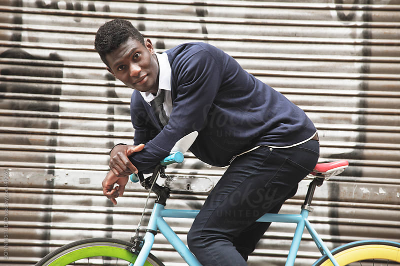 African young man riding a bicycle in the city. by BONNINSTUDIO for Stocksy United
