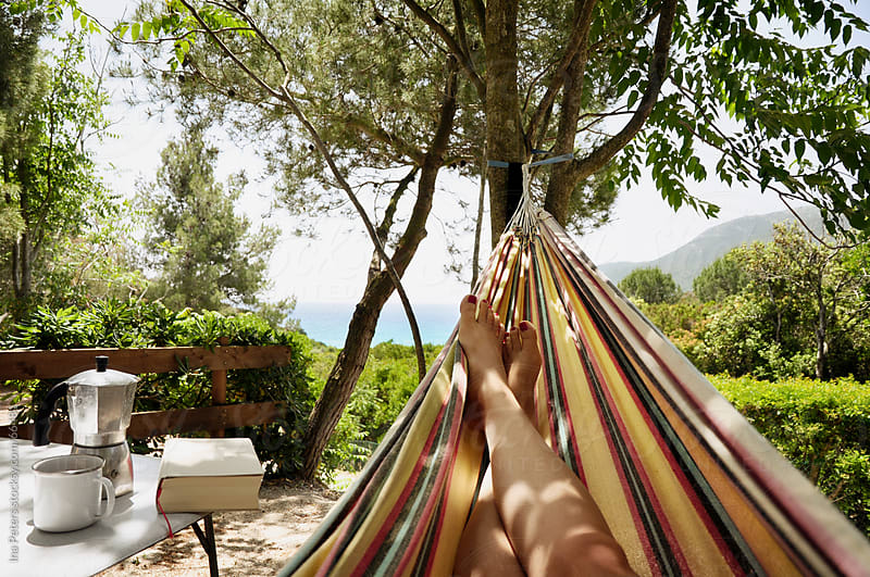 Relaxation lying in hammock with sea view by Ina Peters for Stocksy United