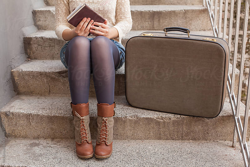 Anonymous Woman Sitting on the Stairs With a Suitcase by Mosuno for Stocksy United