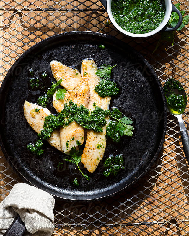 Roasted chimichurri fish with pesto and parsley by Trent Lanz for Stocksy United