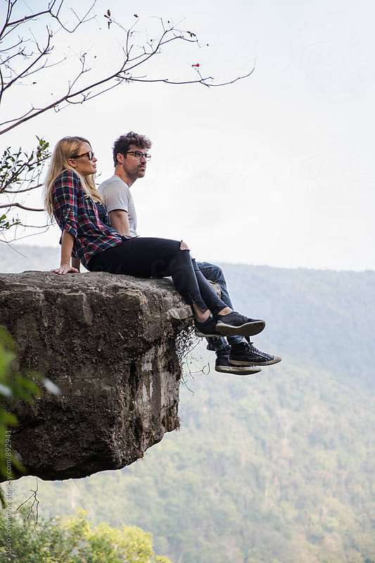 Young couple relaxing on top of a mountain and enjoying valley view by Jovo Jovanovic for Stocksy United