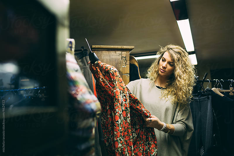 Young woman choosing a dress in a clothing store by michela ravasio for Stocksy United
