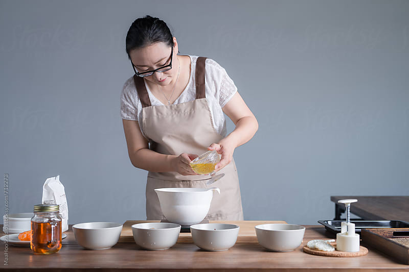 A young woman weighing oil while baking moon cake by Maa Hoo for Stocksy United