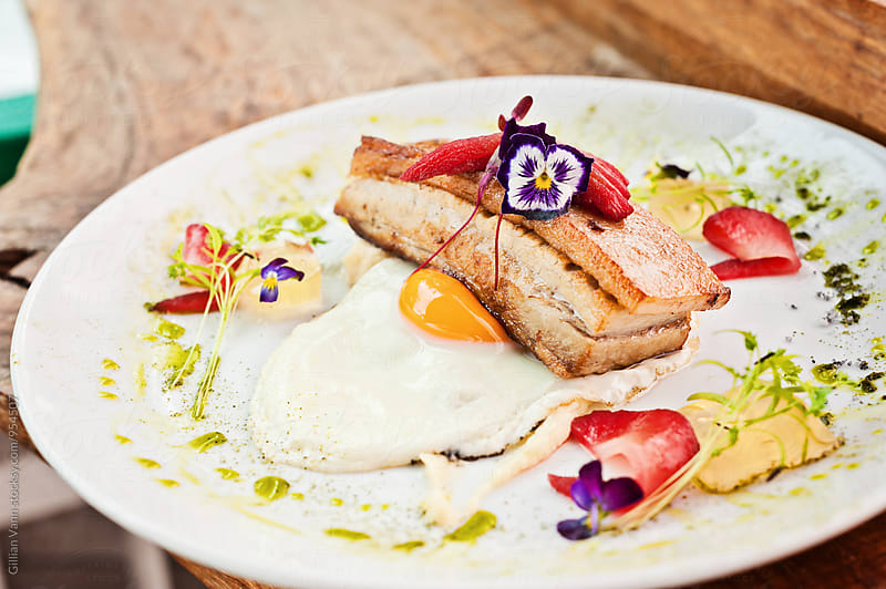 breakfast of pork belly and fried egg, with herb oil and edible flowers by Gillian Vann for Stocksy United