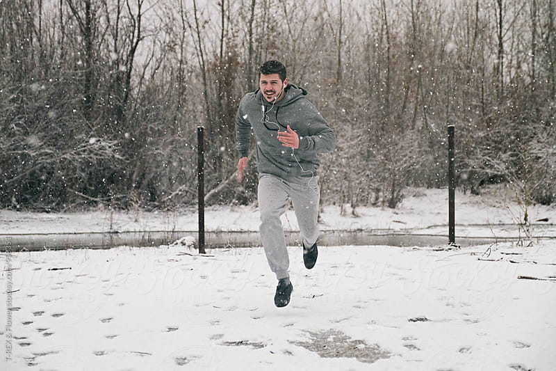 Bearded man running fast in winter by Danil Nevsky for Stocksy United