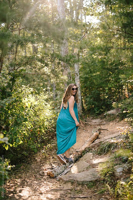 Girl in teal dress walks up pathway by Simone Anne for Stocksy United