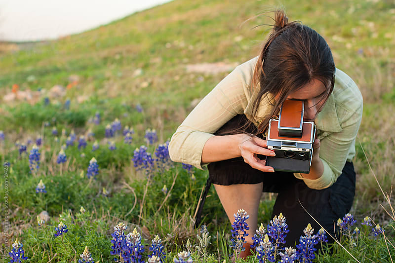 Woman Photographing Flowers with Polaroid Camera by Geoffrey Hammond for Stocksy United
