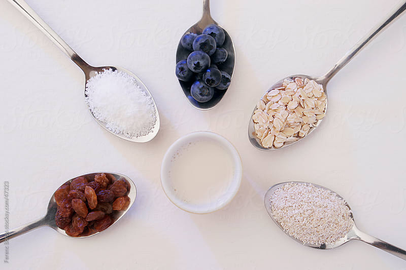 Healthy breakfast ingredients in spoons by Ferenc Boros for Stocksy United
