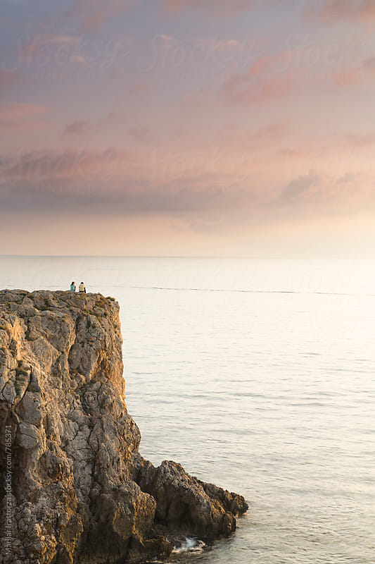 Young couple on a cliff enjoying the sunset by Marilar Irastorza for Stocksy United