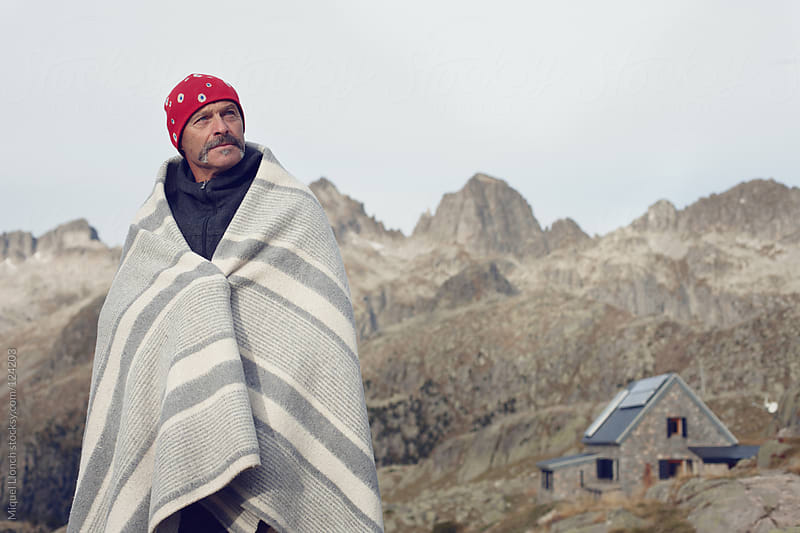 Portrait of a mountain hut guardian with blanket and hat by Miquel Llonch for Stocksy United