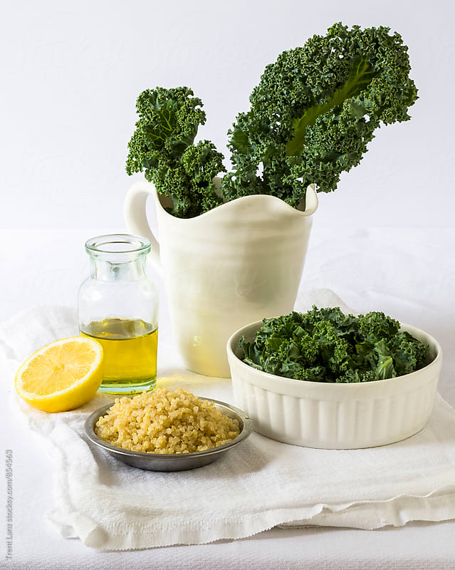 Green kale salad, olive oil, half of lemon and raw millet cereals by Trent Lanz for Stocksy United