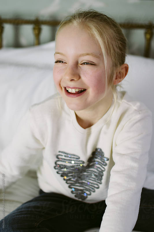 A little girl laughing by Helen Rushbrook for Stocksy United