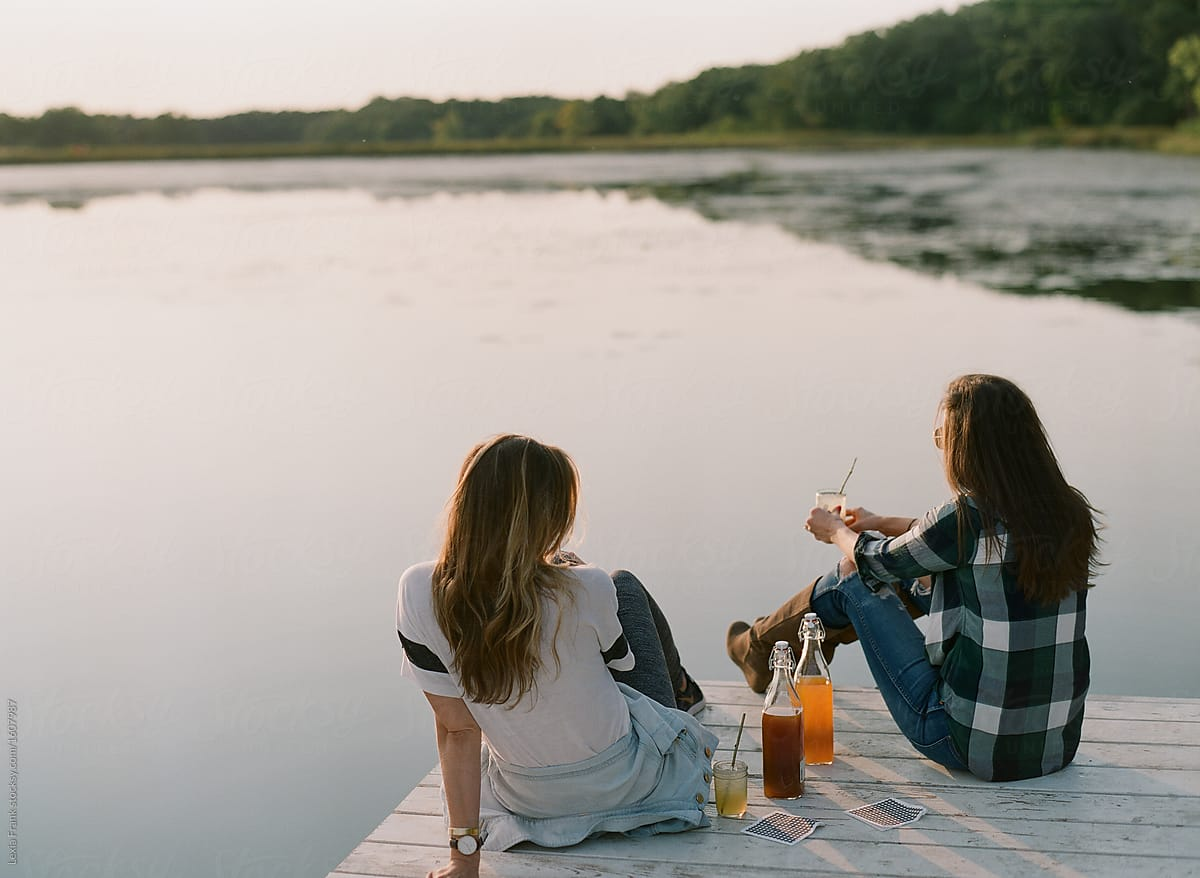 Women Sitting On Dock With Drinks by Lexia Frank