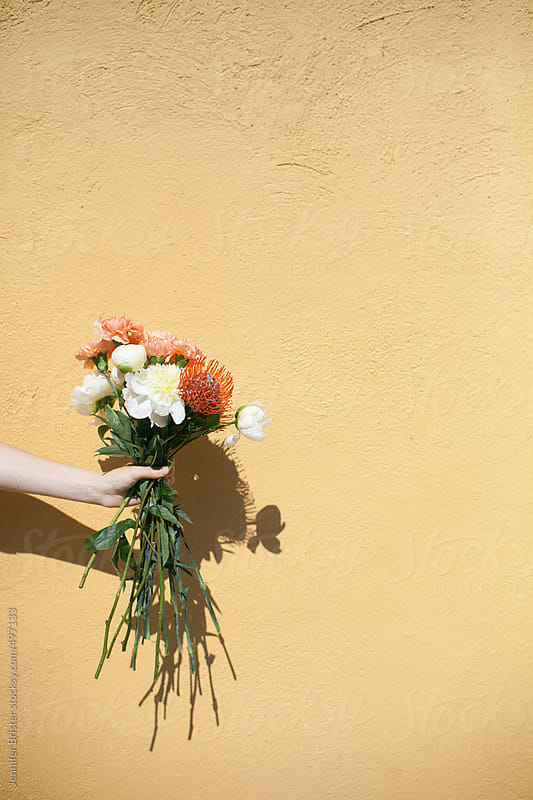 Hand holding bouquet of flowers in front of yellow wall.  by Jennifer Brister for Stocksy United