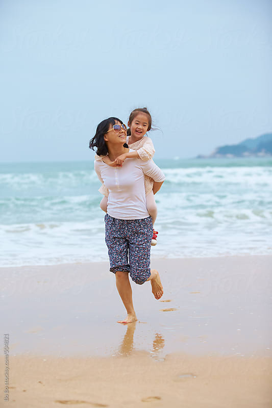 young asian woman with her kid on beach by Bo Bo for Stocksy United
